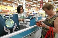 Una clienta paga en la caja de un Carrefour