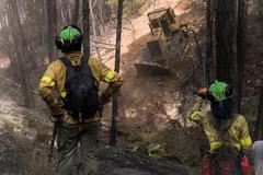 Do especialistas del Plan Infoca trabajan en la extinción de un incendio en la Sierra de Aracena (Huelva), en una imagen de archivo.