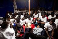 Un grupo de inmigrantes en un barco espera para atracar en Italia.