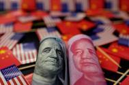 Un dólar y un yuan, sobre banderas estadounidénses y chinas.