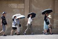 Unos turistas pasean por  Córdoba protegidos del sol con una sombrillas.