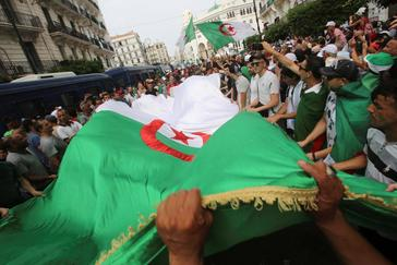 Demonstrators carry flags during a protest demanding the removal of the ruling elite in Algiers