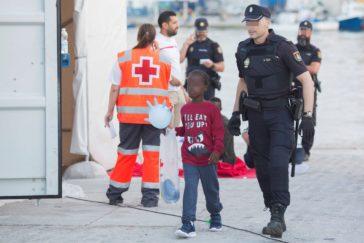 Un menor llegado en una patera, acompañado por una agente de la Policía en Málaga.