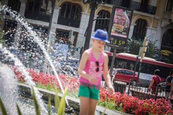 Una niña se refresca en una fuente de Valencia.