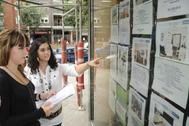 Dos mujeres comparan los precios de una inmobiliaria en Amuriza.