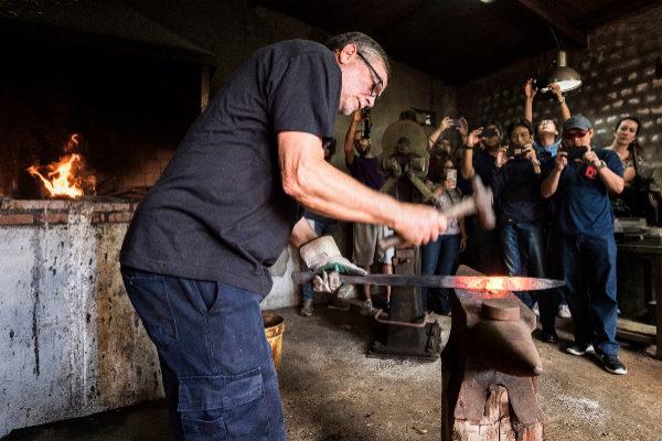 Turistas en un taller de forja de espadas en Toledo.