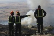 Tres responsables de Bomberos observan la evolución del incendio de Miraflores.