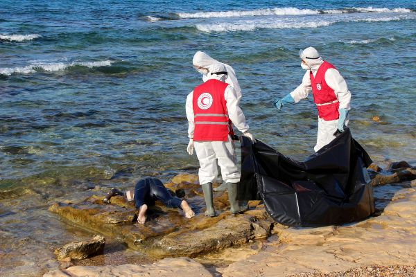 Libyan Red Crescent workers stand near the body of a migrant, who died...
