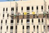 Varios operarios trabajan en la construcción de viviendas de alquiler.