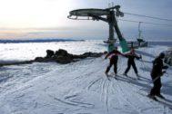 Tres esquiadores en Cerro Catedral mientras las nubes cubren el lago Nahuel Huapi.