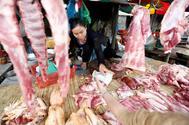 Una comerciante vende carne de cerdo este viernes en un mercado de Phnom Penh, Camboya.