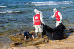 Libyan Red Crescent workers stand near the body of a migrant, who died after their wooden boat capsized, in Khoms