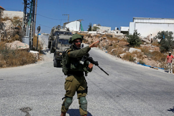 Israeli <HIT>soldier</HIT> gestures during a raid after the Israeli...
