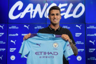 Manchester City's newly signed Portuguese defender Joao <HIT>Cancelo</HIT> poses with a club shirt after attending a press conference during his unveiling at the City Football Academy in Manchester on August 8, 2019. (Photo by OLI SCARFF / AFP)