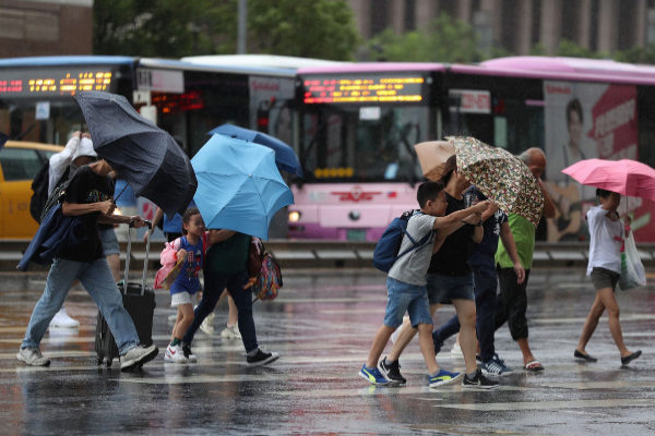 Taipei (Taiwan).- People cross a street during downpour and strong...