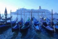 Gondolas, en primer plano, y un crucero al fondo en Venecia