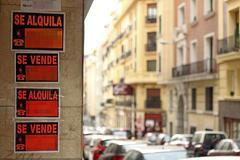 Varios carteles, en un portal, anunciando la venta y el alquiler de inmuebles.