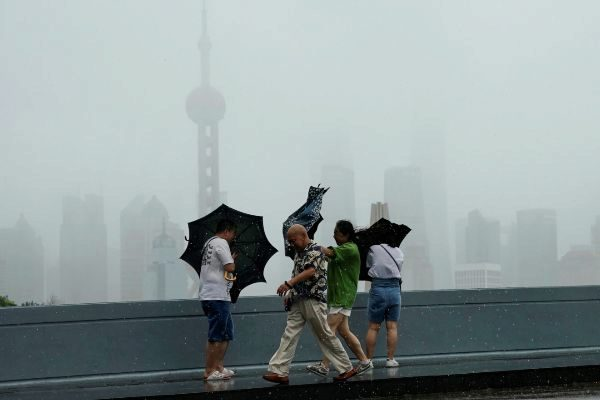 People walk in the rainstorm as typhoon <HIT>Lekima</HIT> approaches...