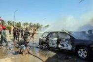 Bomberos libios extinguen las llamas, tras el atentado con coche bomba de este sábado en Bengasi.