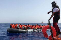 Miembro del barco de rescate 'Ocean Viking' repartiendo chalecos salvavidas entre unos inmigrantes.