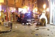 Policías y bomberos junto al coche que se estrelló contra una terraza en Gerona.