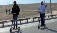 Dos hombres pasean en patinetes eléctricos junto a la playa.