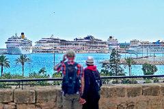 Dos turistas contemplando los cruceros en el Puerto de Palma.