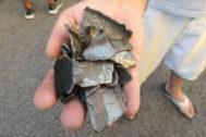 Un hombre sostiene algunos de los fragmentos que cayeron al suelo.