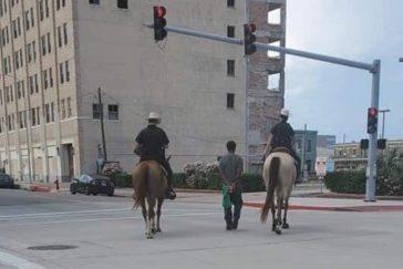 La imagen de la polémica: Donald Neely, de 43 años, camina atado con una cuerda amarrada a sus esposas entre dos policías a caballo, en Galveston (Texas).