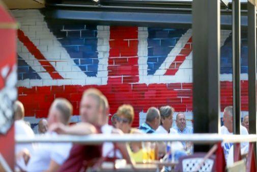 Un 'pub' en la zona inglesa de Benidorm, con una bandera de Reino Unido pintada sobre la pared y varios turistas tomando algo.