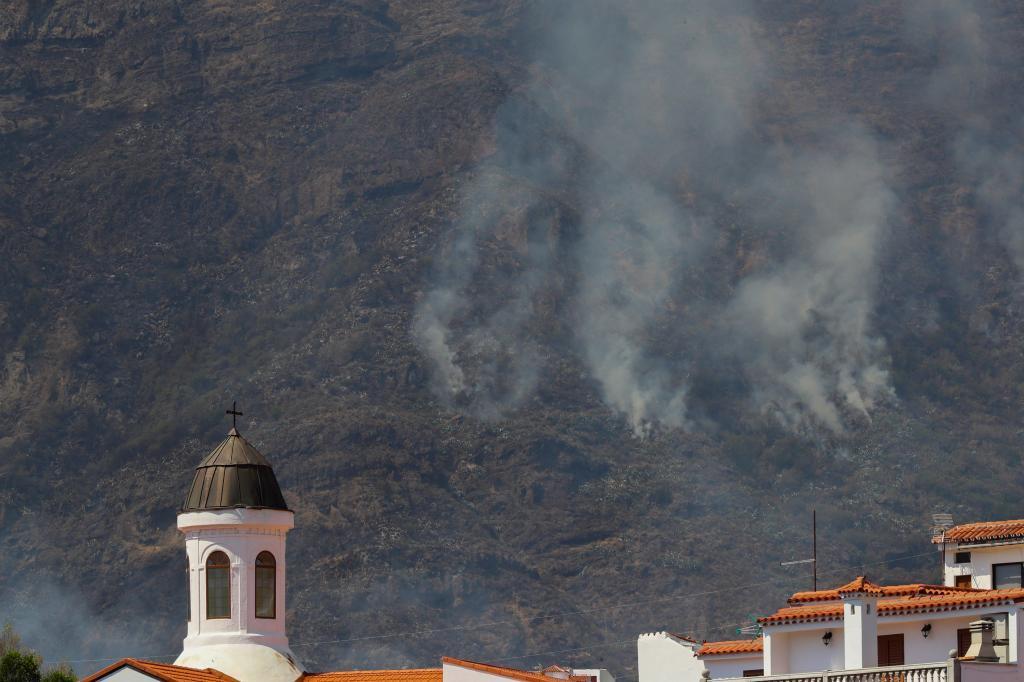 Vista de la cúpula de la iglesia de Tejeda y dentrás uno de los focos del incendio que ha arrasado  los municipios de Tejeda, Artenara y Gáldar, en Gran Canaria.
