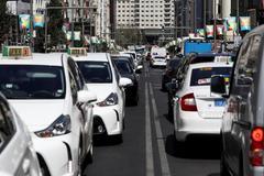 Varios vehículos circulan por una calle de Madrid.