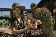 Mercedes García, la creadora de Desert City, con algunos ejemplares en el jardín de cactus.