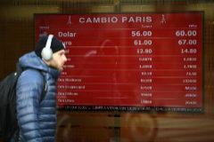 Un ciudadano pasea frente a un escaparate de una casa de cambio en Buenos Aires.