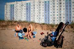 Dos mujeres juegan con sus hijos en la orilla del río Dvina Septentrional, en la región de Severodvinsk.