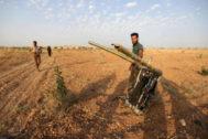 Un combatiente rebelde permanece cerca de los restos del avión de guerra derribado en Jan Sheijun, provincia de Idlib, Siria.