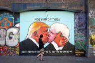 Un hombre pasea frente a un mural de Donald Trump y Boris Johnson en la localidad británica de Bristol.