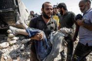 Un hombre lleva el cuerpo de un niño fallecido en un bombardeo del régimen en Idlib.