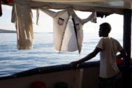 """n migrante mira este domingo desde la cubierta de el buque """"Open Arms"""" las costas italianas de Lampedusa."""