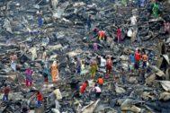 Un grupo de personas busca entre los restos de un incendio que arrasó sus hogares en una barriada de Dacca, Bangladesh.