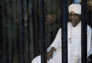 Sudan's former president Omar Hassan al-<HIT>Bashir</HIT> sits guarded inside a cage at the courthouse where he is facing corruption charges, in Khartoum