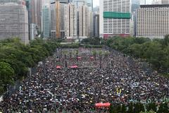 Una multitud se refugia de la lluvia bajo paraguas durante la nueva marcha contra el gobierno en Hong Kong.