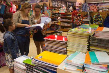 Una madre revisa el material escolar con sus hijas en un centro comercial.