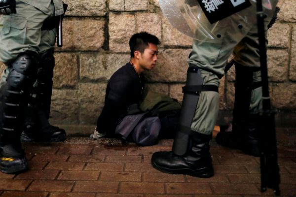 Riot police officers detain an anti-extradition bill protester during...