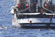 Varios migrantes saltan por la borda del Open Arms.