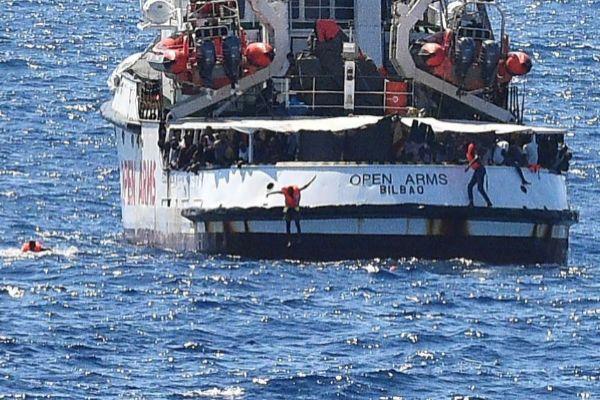 Varios inmigrantes se lanzan al agua esta mañana desde la cubierta...