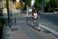 Mujer circulando en patinete por una de las aceras de Madrid