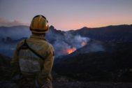 Un bombero observa, ayer, las llamas que se elevan desde el incendio forestal de Gran Canaria.