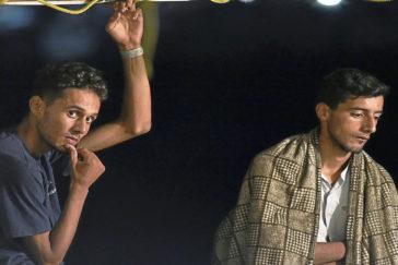 Dos migrantes desembarcan del Open Arms en Lampedusa.