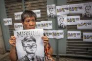 Una activista sostiene una pancarta con una ilustración de Simon Cheng.